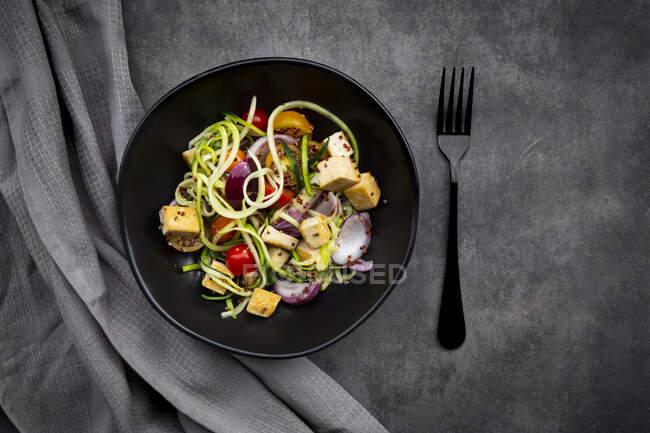 Zucchini con tofu frito, quinao rojo, cebolla y tomate - foto de stock
