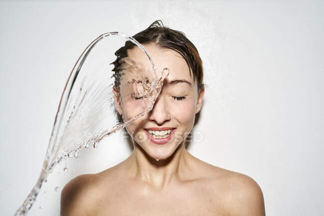 Retrato de una joven riendo con agua salpicada - foto de stock
