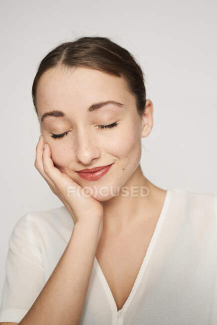 Portrait of smiling young woman with head in hand and eyes closed — Stock Photo