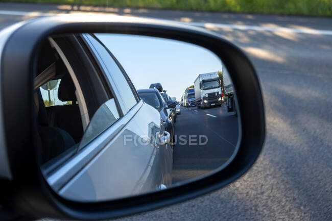 Wing mirror, rescue lane, cars and trucks during traffic jam in the evening, Germany — Stock Photo