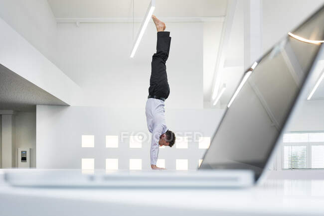 Бизнесмен делает стойку на руках у ноутбука в офисе — стоковое фото