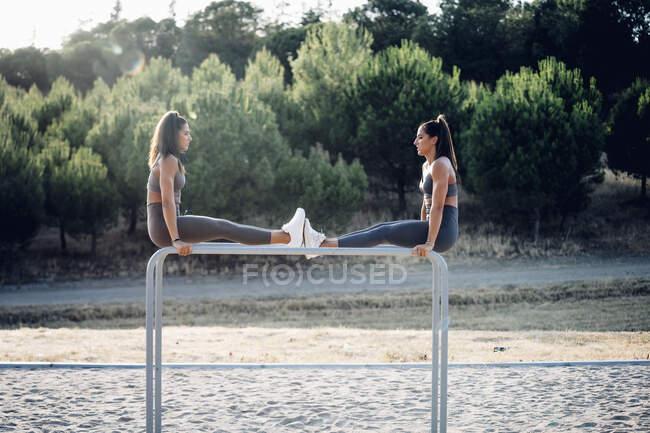 Две сестры-близнецы тренируются на параллельных брусьях — стоковое фото