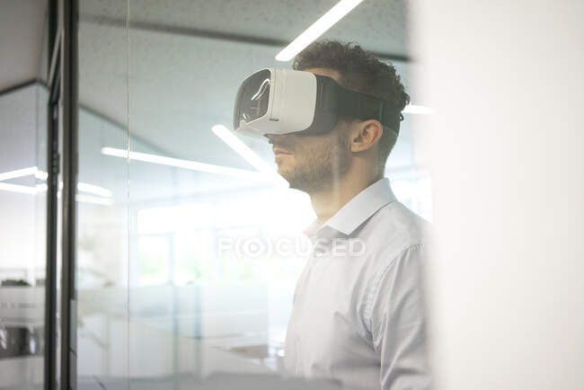 Businessman wearing VR glasses in office — Stock Photo