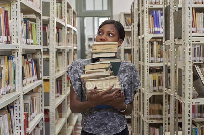 Jeune femme avec pile de livres à la Bibliothèque nationale, Maputo, Mocthe — Photo de stock