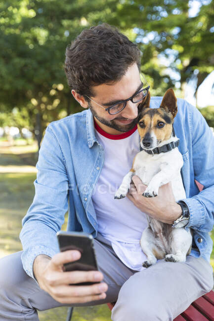 Young man sitting on park bench with his dog taking selfie with smartphone — Stock Photo