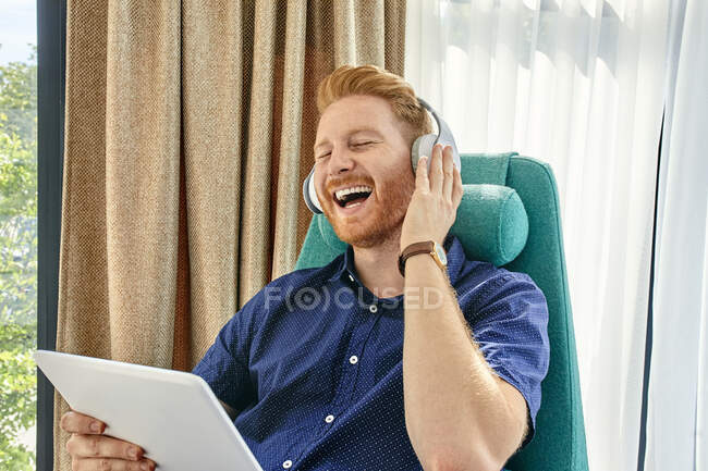 Молодой человек сидит в кресле, слушает музыку, используя цифровой планшет — стоковое фото