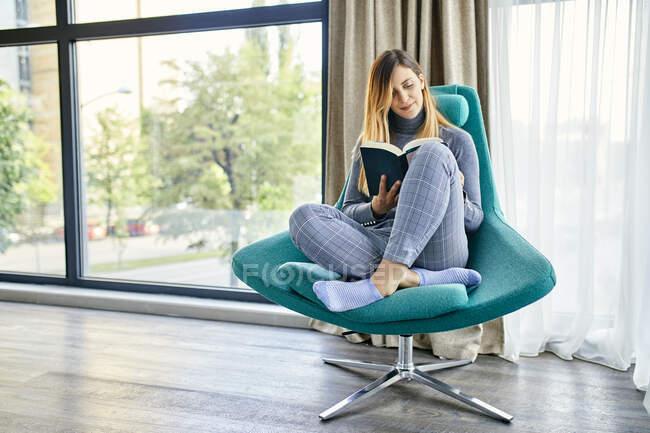 Mujer sentada en sillón, libro de lectura - foto de stock
