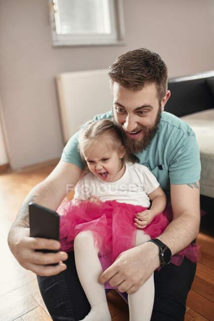 Батько з дочкою роблять селфі, дівчата в рожевому туту. — стокове фото