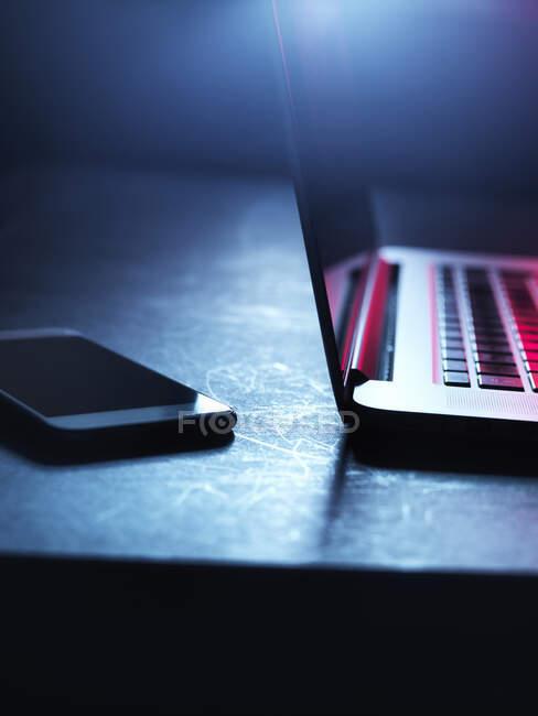 Ноутбук і смартфон вночі. — стокове фото