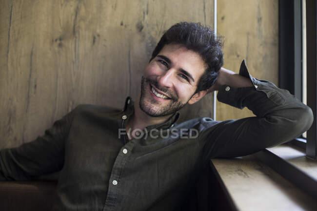 Porträt eines lachenden Mannes mit dem Kopf in der Hand — Stockfoto