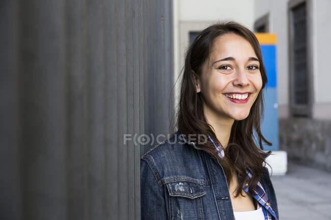 Junge lächelnde Frau blickt in die Kamera, steht an der Wand — Stockfoto