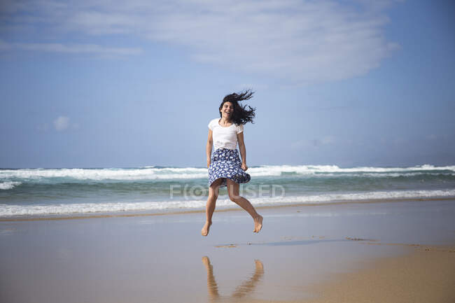 Laughing woman jumping in the air on the beach, Fuerteventura, Spain — Stock Photo