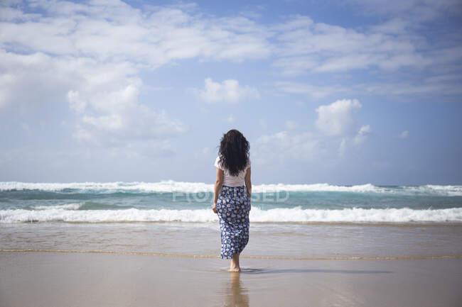Visão traseira da mulher em pé na praia olhando para o mar, Fuerteventura, Espanha — Fotografia de Stock