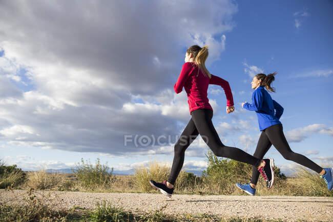 Женщины бегают вместе в сельской местности — стоковое фото