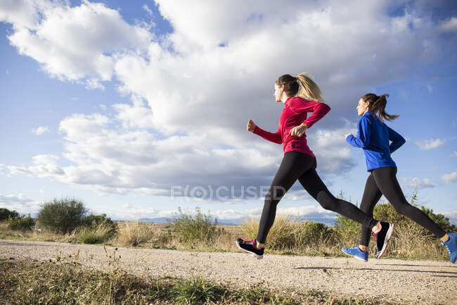 Jovens mulheres a correr juntas no campo — Fotografia de Stock