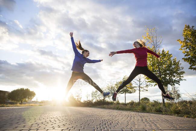 Молодые женщины веселятся и прыгают в парке под утренним солнцем — стоковое фото
