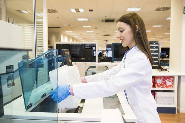 Vue latérale de la jeune femme en blouse de laboratoire versant des flacons d'échantillons de sang dans le réfrigérateur tout en travaillant dans un laboratoire de recherche — Photo de stock