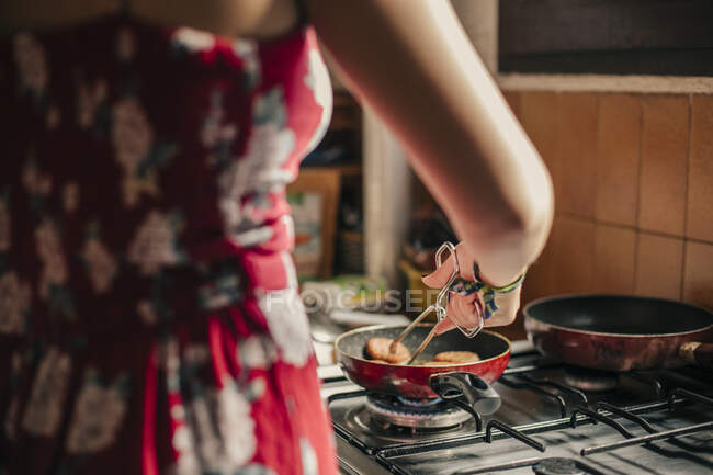 Close-up of woman cooking in kitchen using a pan — Stock Photo