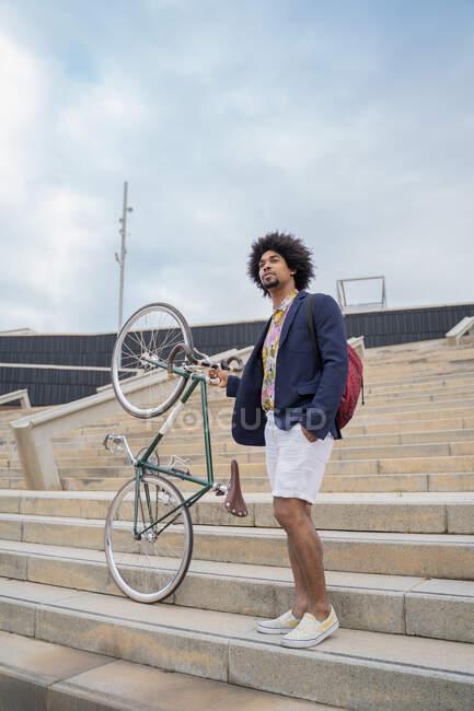 Homem elegante com bicicleta nas escadas da cidade — Fotografia de Stock