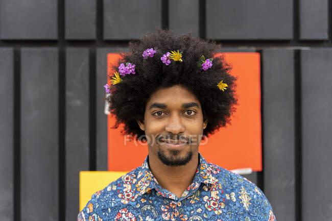 Retrato de hombre con flores en el pelo con camisa de colores - foto de stock