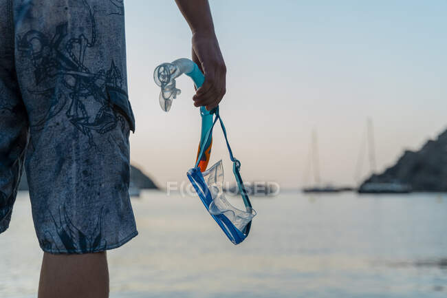 Young man with snorkel and diving goggles at the beach in the evening — Stock Photo