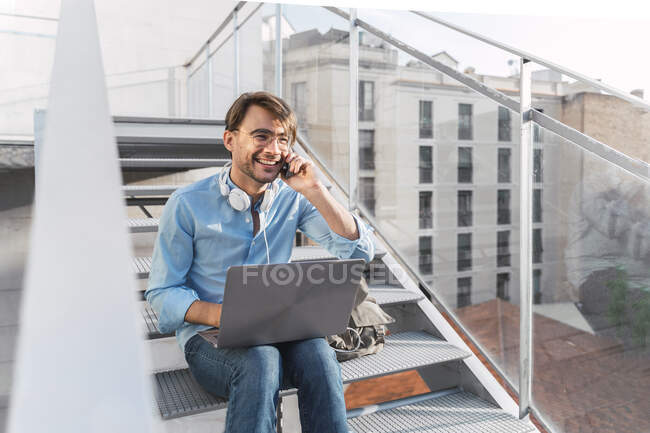 Casual businessman sitting on stairs with laptop talking on the phone — Stock Photo