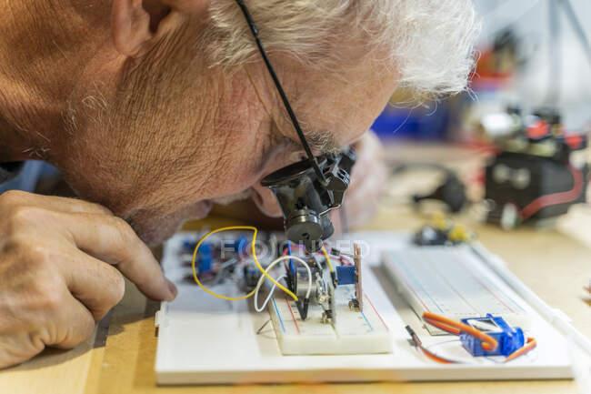 Homem sênior trabalhando em circuitos eletrônicos em sua oficina — Fotografia de Stock