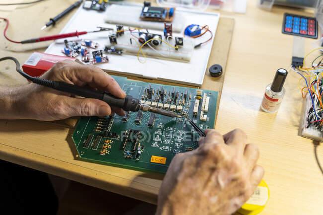 Älterer Mann arbeitet in seiner Werkstatt an elektronischen Schaltungen, aus nächster Nähe — Stockfoto