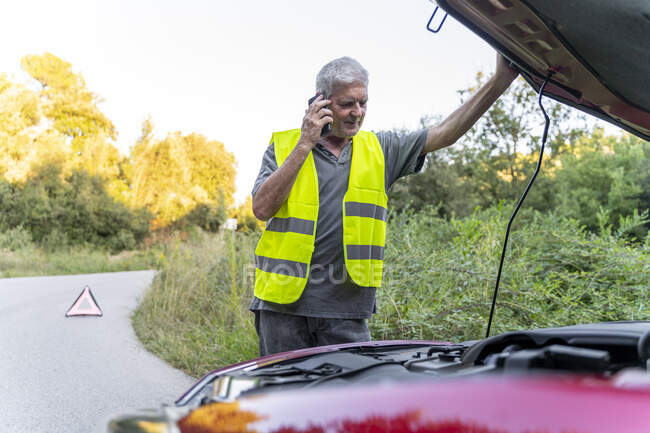Hombre mayor de pie en su coche roto con un chaleco de seguridad y usando su teléfono inteligente - foto de stock