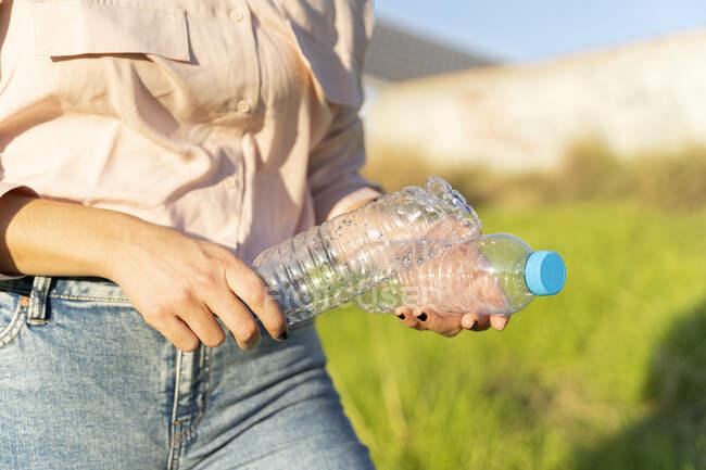 Mãos de mulher segurando garrafas de plástico vazias, close-up — Fotografia de Stock