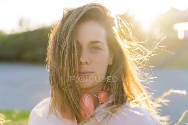 Ritratto di giovane donna con i capelli che soffiano alla retroilluminazione — Foto stock