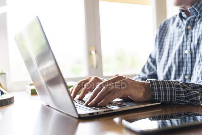 Homem sênior usando laptop em casa — Fotografia de Stock