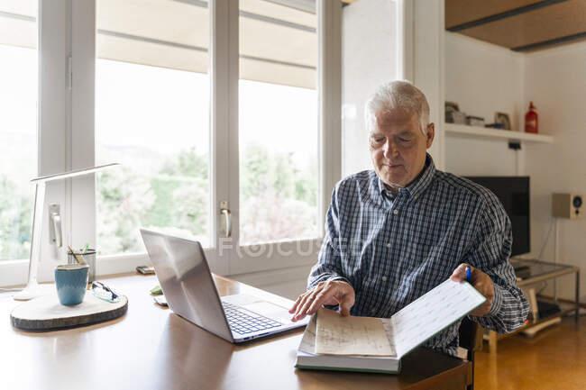 Старший сидит дома перед ноутбуком и переворачивает страницы в блокноте — стоковое фото