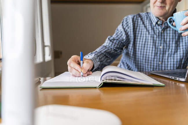 Senior man sitting at home in front of laptop making notes — Stock Photo