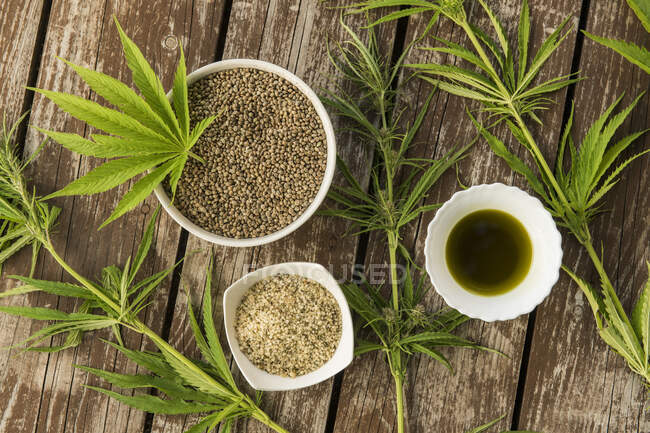 Hemp leaves, seeds and oil from above on wooden background — Stock Photo