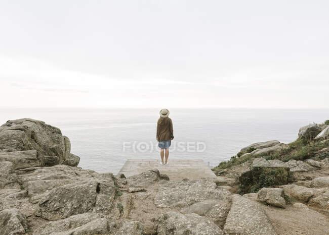 Жінка з камерою, що стоїть на скелі, дивиться на море. — стокове фото