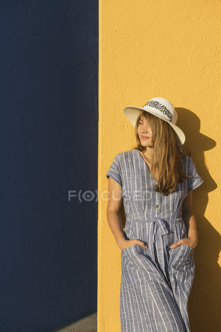 Woman standing in front of yellow and blue walls — Stock Photo