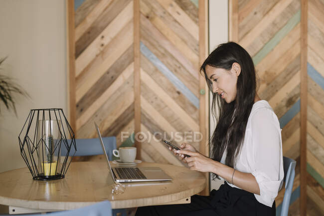 Young businesswoman using laptop and cell phone at table in a cafe — Stock Photo
