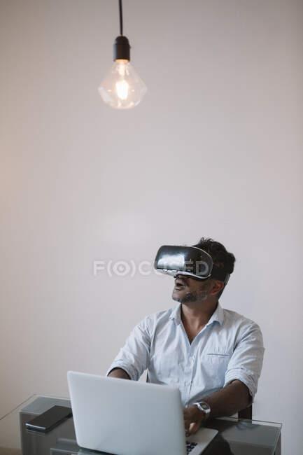 Businessman sitting at table testing VR simulator — Stock Photo