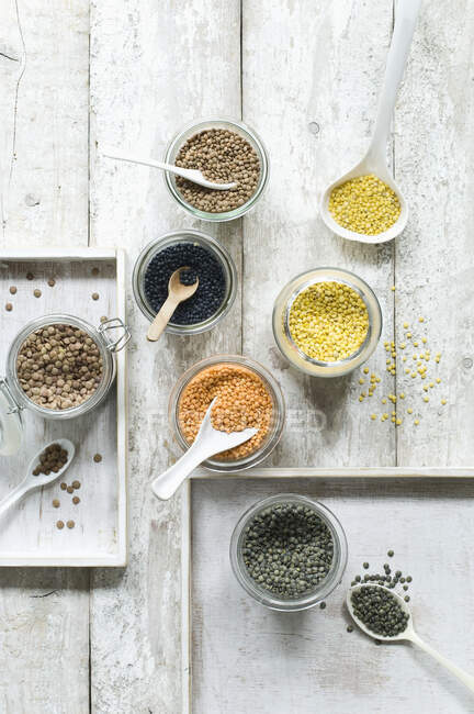 Assorted lentils on wooden table seen from above — Stock Photo