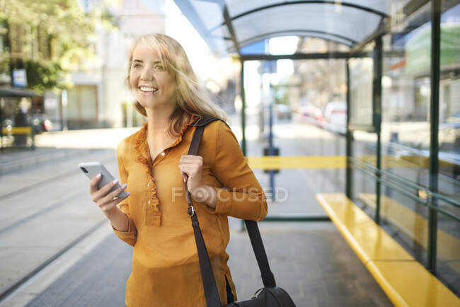 Smiling young woman with smartphone waiting for the tram at tram stop — Stock Photo