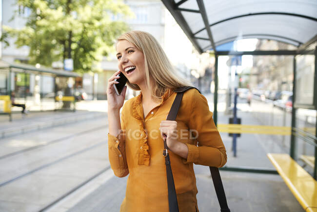 Happy young woman on the phone at tram stop — Stock Photo