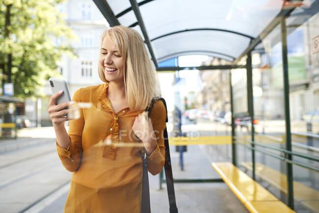 Усмішка молода жінка за допомогою смартфона на трамвайній зупинці. — стокове фото