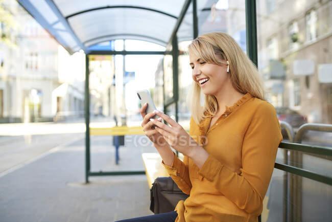 Щаслива молода жінка з бездротовими навушниками на автобусній зупинці. — стокове фото