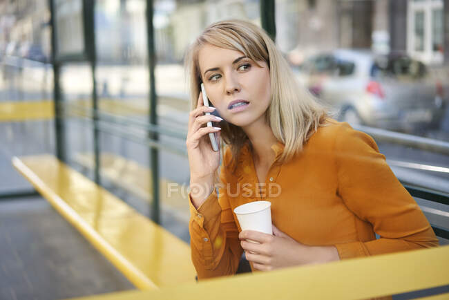 Young woman with smartphone and takeaway coffee waiting for the bus at bus stop — Stock Photo