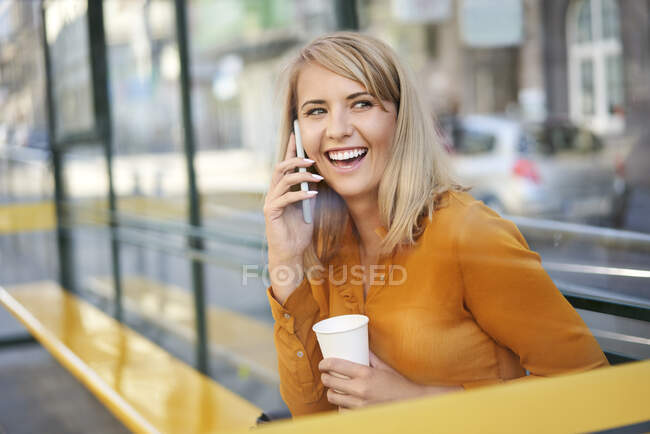 Happy young woman with smartphone and takeaway coffee at bus stop — Stock Photo