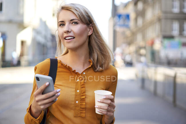 Smiling young woman with smartphone and takeaway coffee in the city — Stock Photo