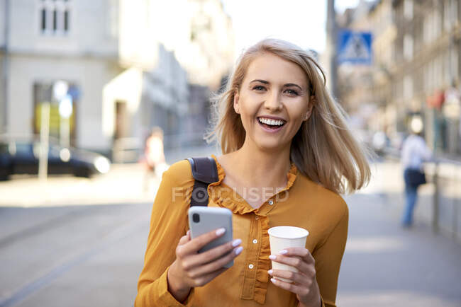Portrait of happy young woman with smartphone and takeaway coffee in the city — Stock Photo