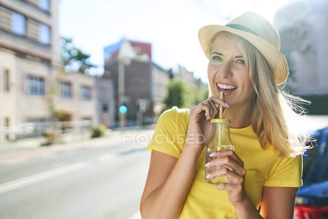 Happy young woman enjoying a drink in the city — Stock Photo
