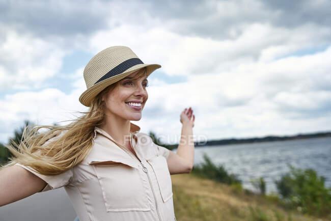 Mujer feliz en la orilla del lago - foto de stock